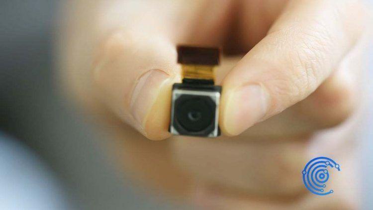 Mano sujetando una mini cámara espía