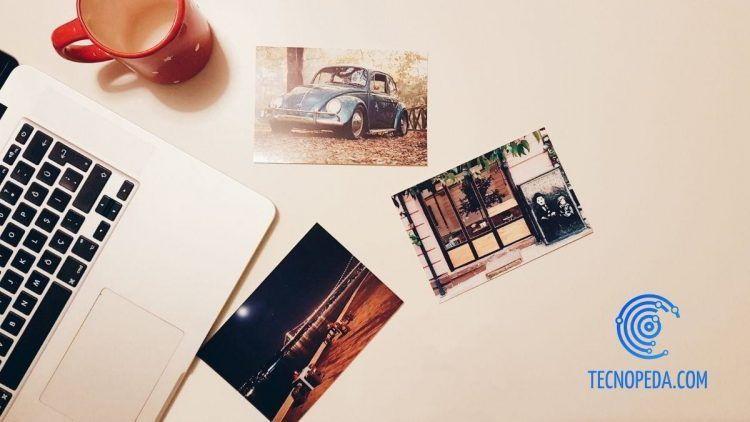Fotografías sobre una mesa junto a un portátil